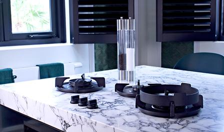 Een mooi gemonteerde witte keuken met een mooi marmeren achterwand