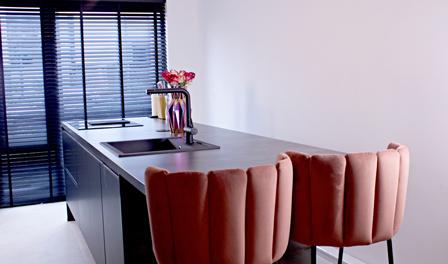 Een mooi gemonteerde witte keuken met een mooi marmeren look blad